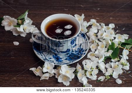 Cup Of Tea With Jasmine Flowers On The Dark Laminate. The Fragrant Jasmine Flower Cup Of Jasmine Tea