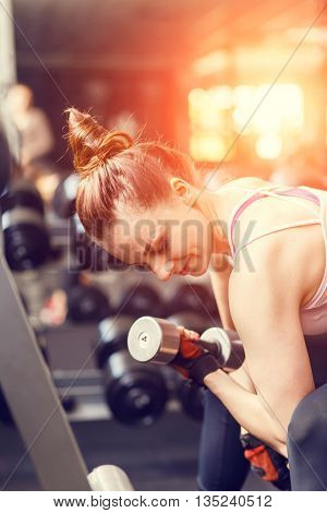 Young Woman Doing Exercise With Dumbbells In A Gym