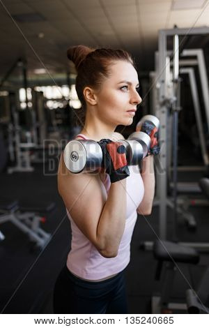 Young Woman Doing Exercises With Dumbbells In Gym