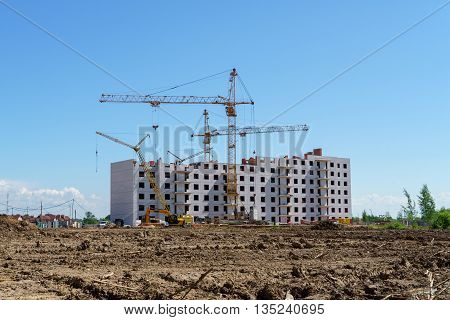 The construction of a multistory building. Construction cranes are on the building site