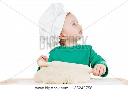Smiling little cook boy kneading the dough for the cookies isolated on white background. Half-length portrait of the table in studio