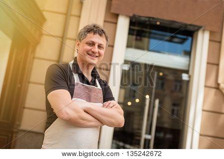 baker concept. Happy baker standing near her  bakery