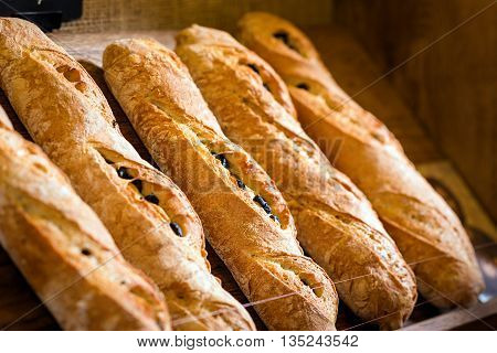 baker concept. closeup of some baguettes or bread rolls on a wooden table in bakery. Fresh baguettes with olive