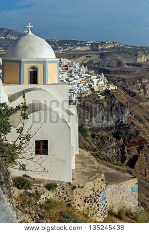 Orthodox church in town of Firostefani and panoramic view of Santorini island, Thira, Cyclades, Greece