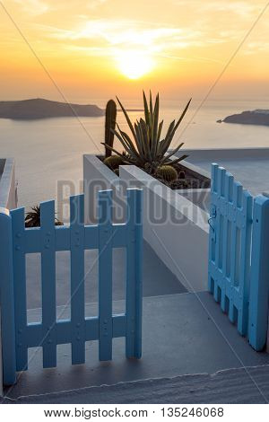 Entrance of white house and sunset in town of Imerovigli, Santorini island, Thira, Cyclades, Greece