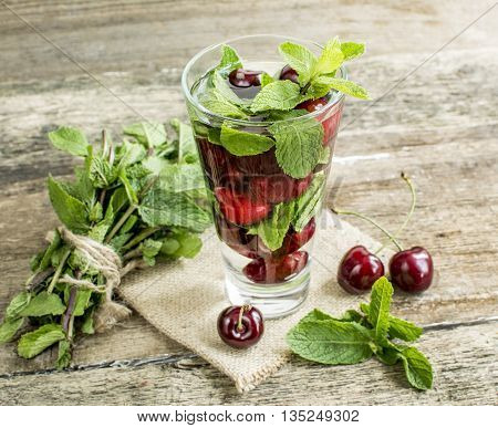 detox water with cherries and mint in a glass on a background of leaves of mint and strawberries on a wooden table close-up