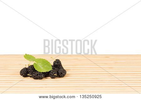 Heap of ripe black mulberries with green leaves on table on white isolated background with option to insert your product . Horizontal composition