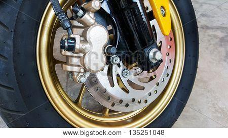 Closeup at disk brake and wheel of the motorcycle.