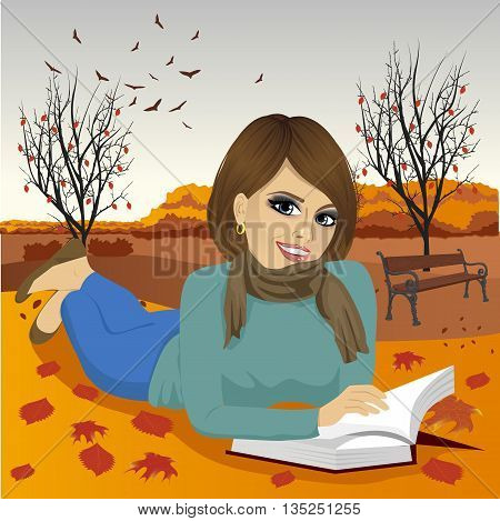 Gorgeous brunette woman reading a book in the autumn park