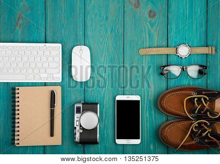 Shoes, Camera, Smartphone, Notepad, Watch, Glasses, Keyboard And Pc Mouse On The Blue Wooden Desk