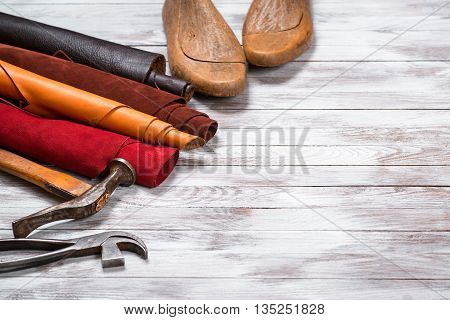 Brightly colored leather in rolls working tools and shoe lasts on the white wooden background. Leather craft. Copy space.