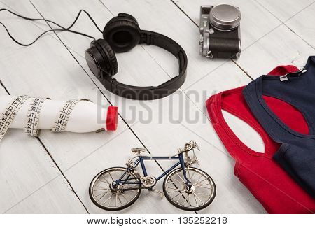 Travel And Sport Concept -  Bicycle Model, Shirts, Headphones, Camera, Bottle Of Water And Centimete