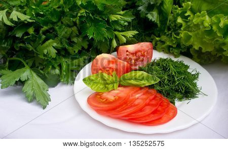 the cut red and pink tomatoes and the cut fennel lie on a plate on a white cloth, greens of other types, parsley, salad and a basil around