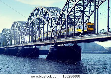 Blue with yellow electric train rides on the railway bridge over the river Daugava in Riga