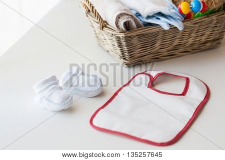 babyhood, childhood, motherhood and object concept - close up of white baby bootees, bib and newborn stuff in basket on table