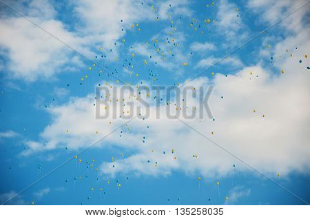 Blue and yellow baloons flying in the blue sky