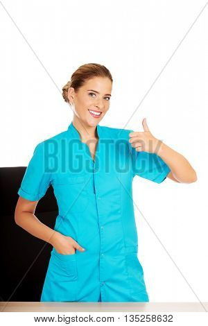 Female doctor standing behind the desk and swhows thumb up