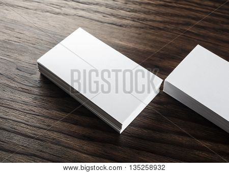 Blank business cards. Photo of blank white business cards on wooden background. Mock-up for design presentations and portfolios. Blank template for ID.