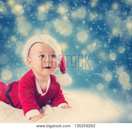 Eight month old baby in santa costume lying on soft blanket with blue background and falling snow