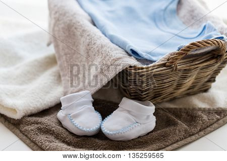 babyhood, motherhood and object concept - close up of white baby bootees with pile of clothes and towel for newborn boy in basket on table