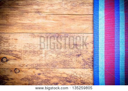 picnic tablecloth on old wooden table top view.