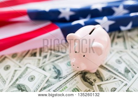 budget, finance, saving and nationalism concept - close up of american flag, piggy bank and dollar cash money