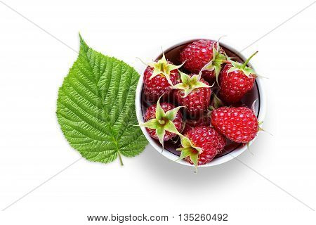 Raspberry in bowl and green leaf isolated on white background
