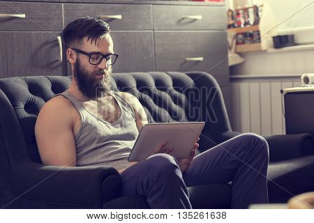 Male model sitting on a couch in a living room surfing the web on a tablet computer