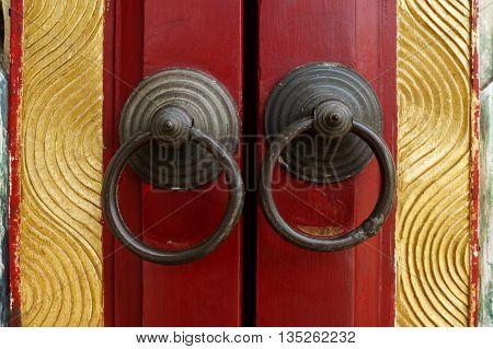 Old door ring handle on red wooden door
