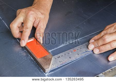 Two hands keep metal angle on steel plate.