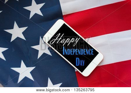 technology, patriotism, anniversary, national holidays and celebration concept - close up of smartphone on american flag and independence day words on screen