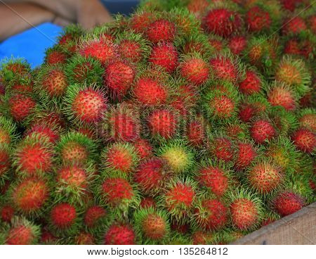 Pile of fuzzy red rambutan fruit for sale, Ranot waterside market, Thailand