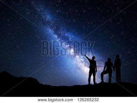 Colorful Milky Way with silhouette of a standing man pointing finger in night starry sky and his parents. Silhouette of a family. Night landscape. Beautiful Universe space background