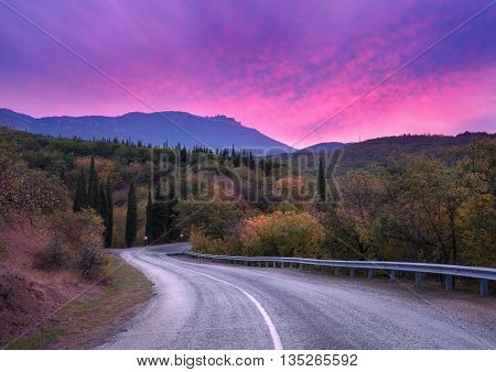 Mountain winding road passing through the forest with dramatic colorful sky and red clouds at dusk in summer. Mountain landscape