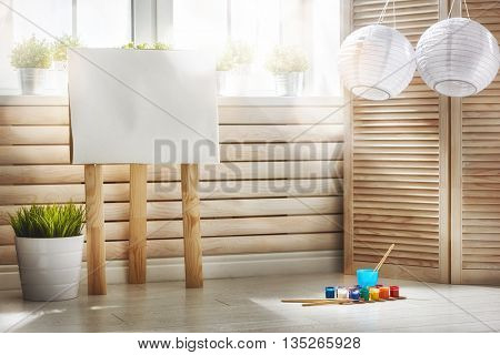 Interior of colorful room for child. an easel and paints for drawing.