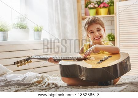 Cute little child girl playing guitar.
