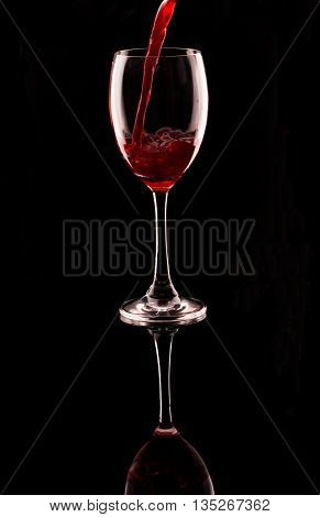 close up pouring red wine into the glass black isolate