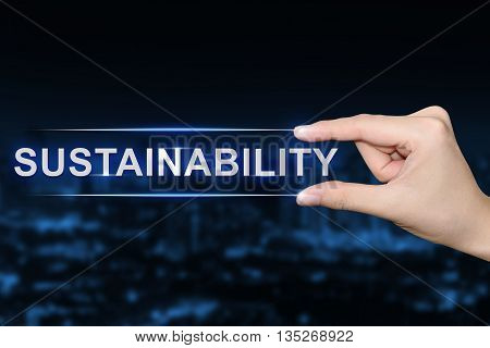 hand pushing sustainability button on blurred blue background