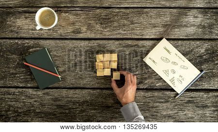 Research and brainstorming - top view of male hand placing wooden cubes in a square shape with charts graphs and notes written on a piece of paper lying on desk with note pad and cup of coffee.