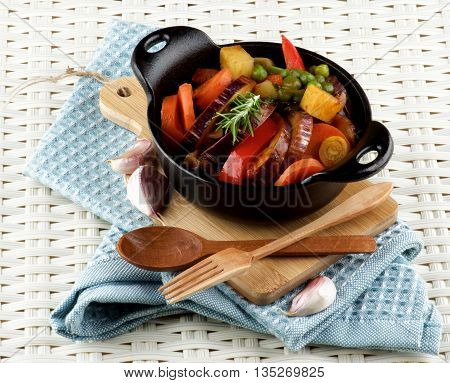 Delicious Homemade Colorful Vegetables Ragout with Striped Eggplant Carrots Potatoes Red Bell Pepper and Green Pea in Black Iron Stewpot with Wooden Fork and Spoon closeup Blue Napkin on Wicker background