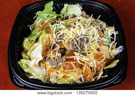 fresh taco salad of seasoned ground beef lettuce tomato and grated cheese on red background
