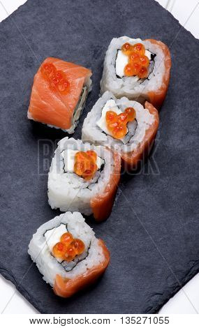 Gourmet Sushi with Smoked Sliced Salmon and Gourmet Red Caviar on Stone Plate closeup on White Plank background. Top View