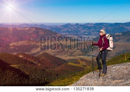 Person with Hiking Backpack and Trekking Poles Staying on High Rock with Mountain View with Autumnal Colors Forest and Blue Sky with Shining Sun