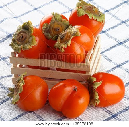 Heap of Delicious Raw Persimmon in Wooden Box closeup on Checkered Textile Napkin