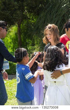 June 12, 2016-Quito, Ecuador.  North American traveler playing with South American children in a Quito, Ecuador, park.