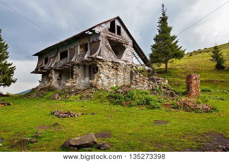 Old dilapidated house made of stones and logs