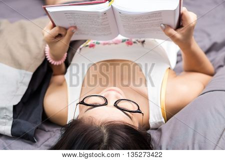 Woman In Cozy Shirt Reading Book On Bed Top View Point