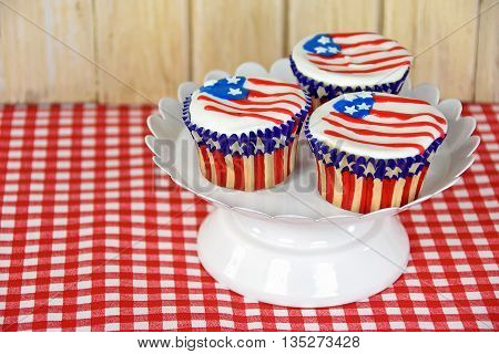 Patriotic cupcakes with flag frosting on white pedestal plate