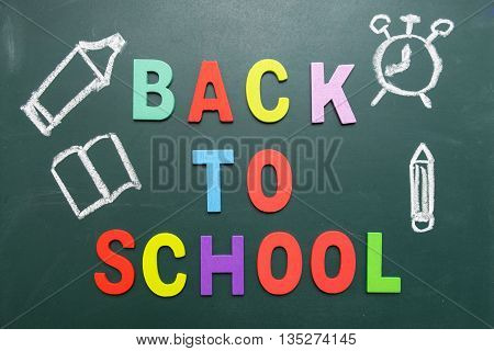 Colorful Back To School wording with hand drawing with chalk of pencil book alarm clock pen on blackboard - Concept of back to school