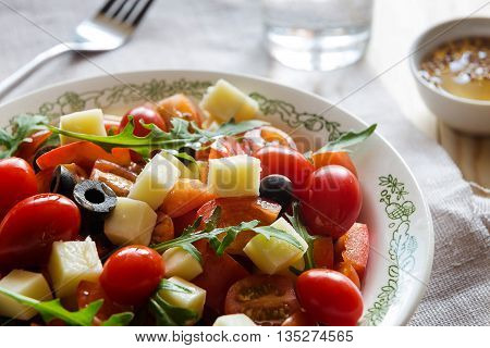 Close up of a plate of vegetable salad with a fork and a glass of water